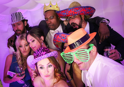 Wedding photography, the bride and groom clown around with their friends in the photo booth.