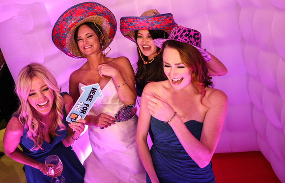 Wedding photography, the bride laughs with her girlfriends in the photo booth. They are wearing sombreros.