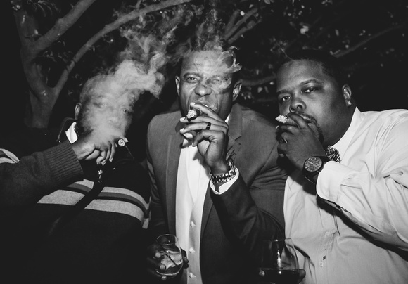 Wedding photography, a black and white image of the groom and two friends smoking cigars.