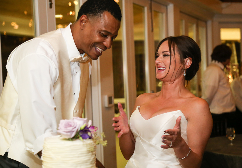 Wedding photography, the bride and groom laugh out loud while sharing their slice of cake.
