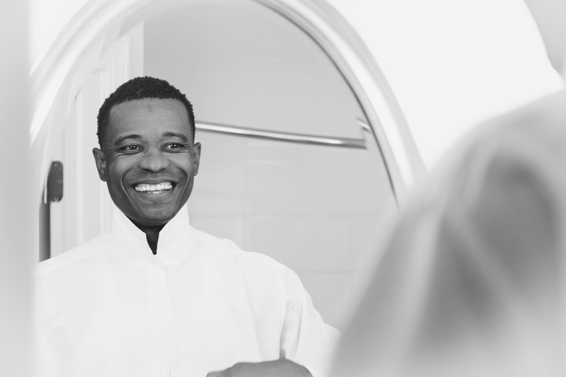 Wedding photography, a black and white image of a groom smiling in the mirror as he buttons his shirt.