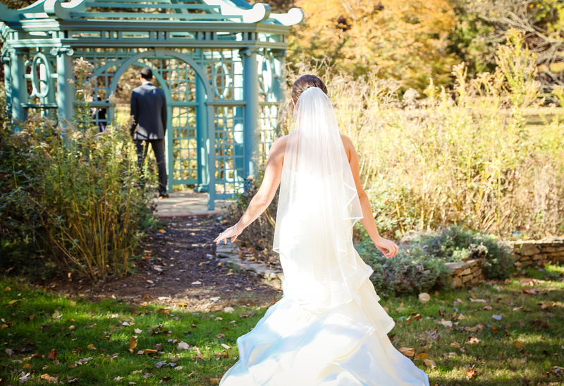 Wedding photography, a bride in a long veil and dress walks towards her groom, standing in a teal gazebo.