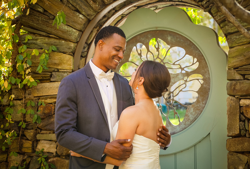 Wedding photography, a groom gazes into his bride's eyes while holding her in front of a stone wall and teal door.