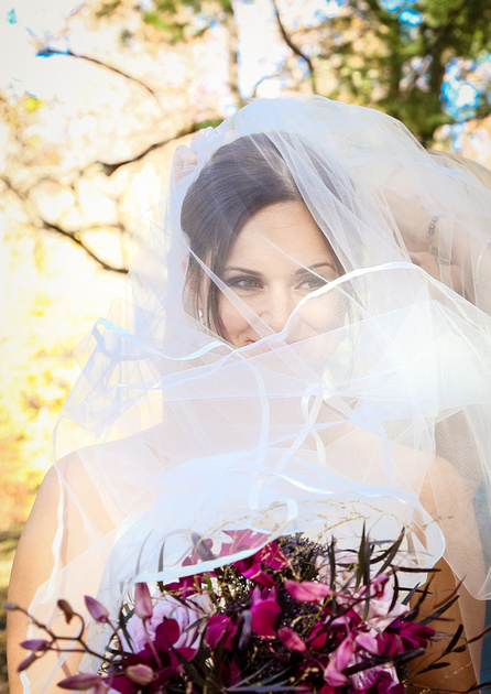 Wedding photography, the bride smiles while holding her bouquet, with her veil over her face.