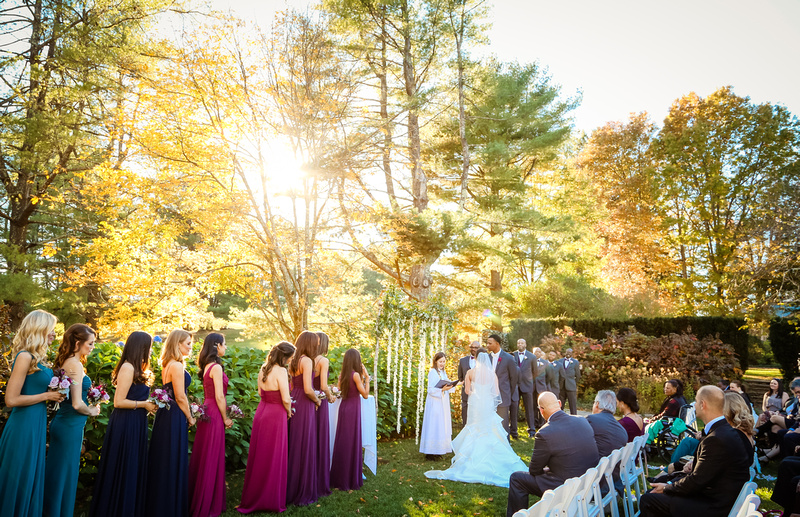 Wedding photography, bright sunshine coming through the yellow trees during a wedding ceremony.