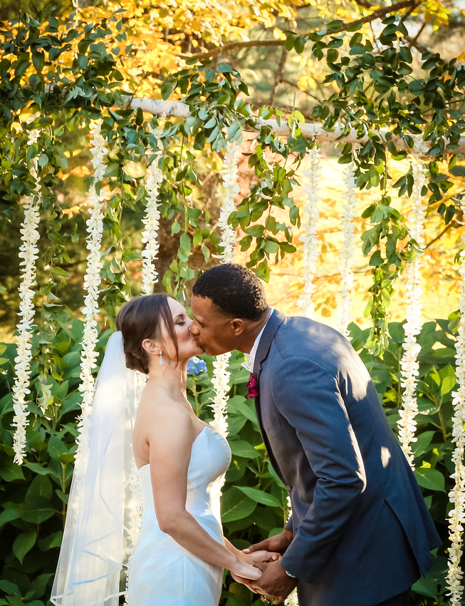 Wedding photography, the bride and groom share their first kiss as husband and wife. Flower petals hang behind them.
