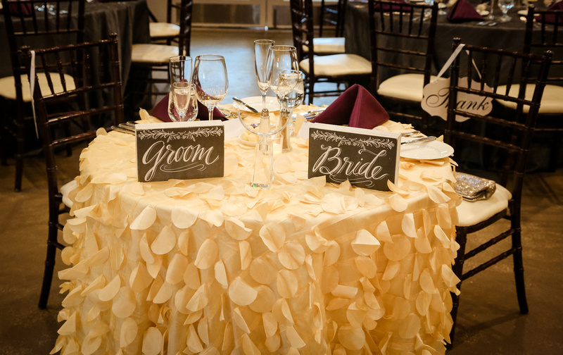 Wedding photography, the sweetheart table, labeled bride and groom, and draped in cream petals.