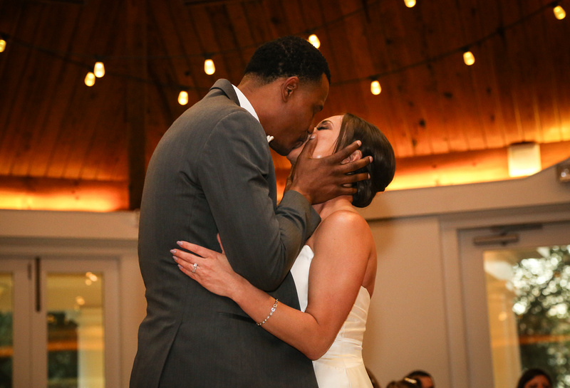 Wedding photography, the bride and groom share a passionate kiss during the first dance.