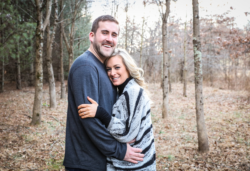 Engagement photography, a blond man and woman embrace each other and laugh at the camera.