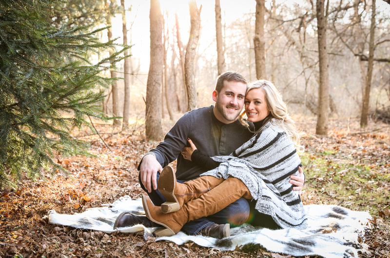 Engagement photography, a couple smiles at the camera while sitting on a blanket in the woods.