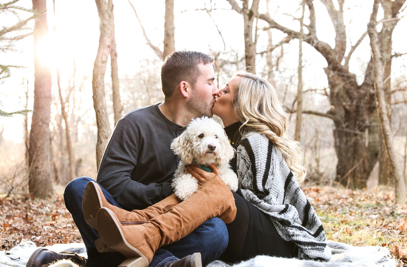Engagement photography, a couple sits in the woods kissing with their small white dog on their laps.