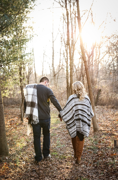 Engagement photography, a couple walks in the woods holding hands. The man has a blanket over his shoulder.