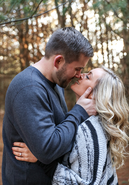 Engagement photography, a couple smiles just before they share a romantic kiss in the woods.