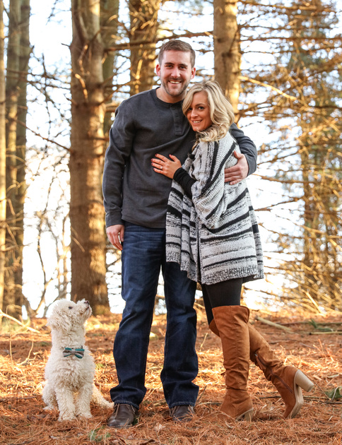 Engagement photography, a couple smiles at the camera while their small white dog looks up at them.
