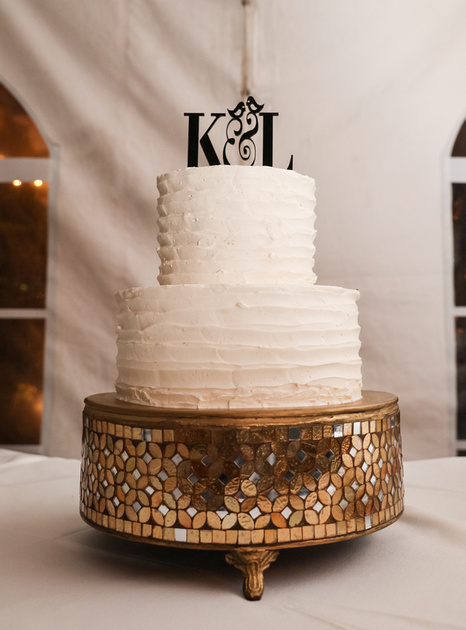 Wedding photography, a white wedding cake with a topper that says K & L with lovebirds on it. The cake sits on an ornate golden platform.