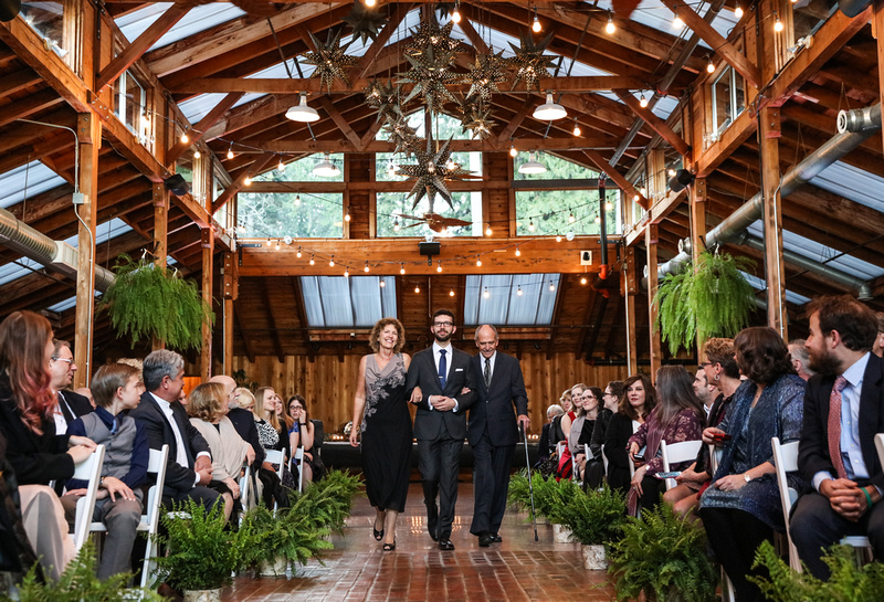 Wedding photography, a groom walks down the aisle with his parents in a elegant log cabin.