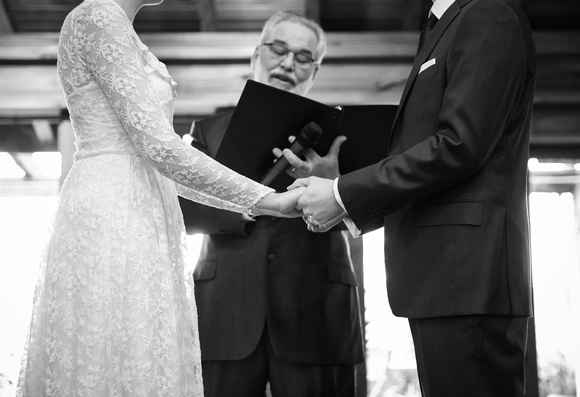 Wedding photography, a closeup of a couple holding hands during their wedding ceremony.