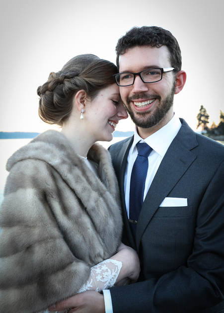 Wedding photography, a groom holds a bride tightly as she puts her forehead on him. She wears a fur stole.