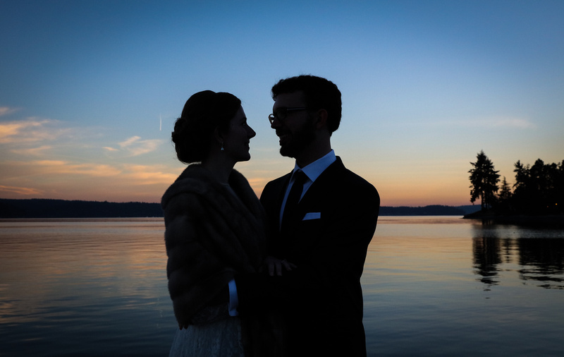 Wedding photography, a silhouette shot of a couple gazing at each other with blue and pink light behind them.