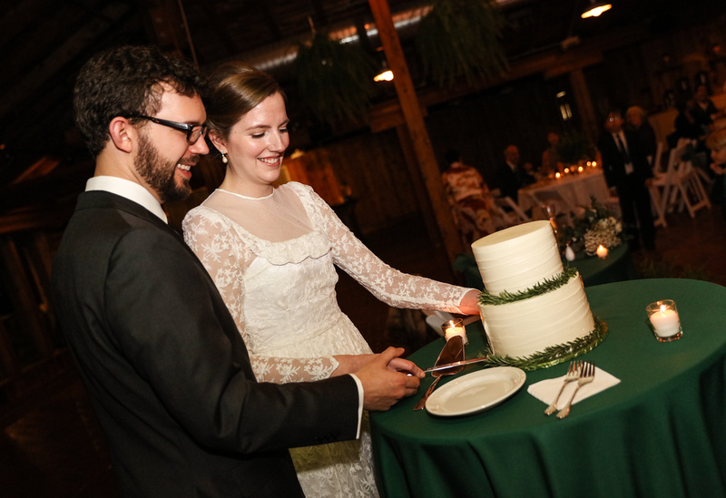 Wedding photography, a bride and groom cut their wedding cake. She wears a lace gown.