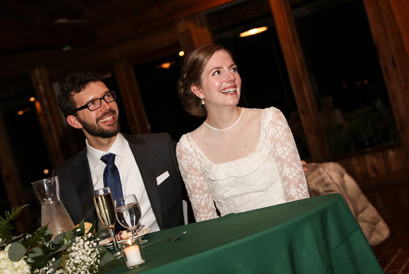 Wedding photography, the bride and groom smile at their green table during toasts.