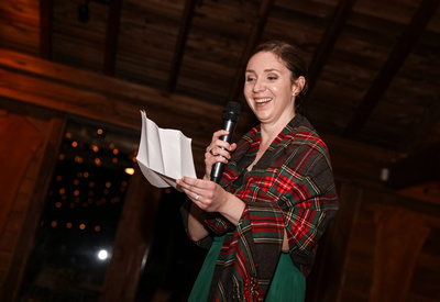 Wedding photography, the maid of honor delivers her speech wearing a red plaid shawl.