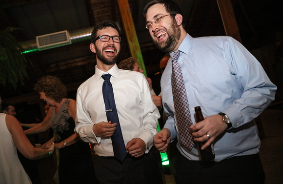 Wedding photography, a groom laughs over beers with one of his friends.