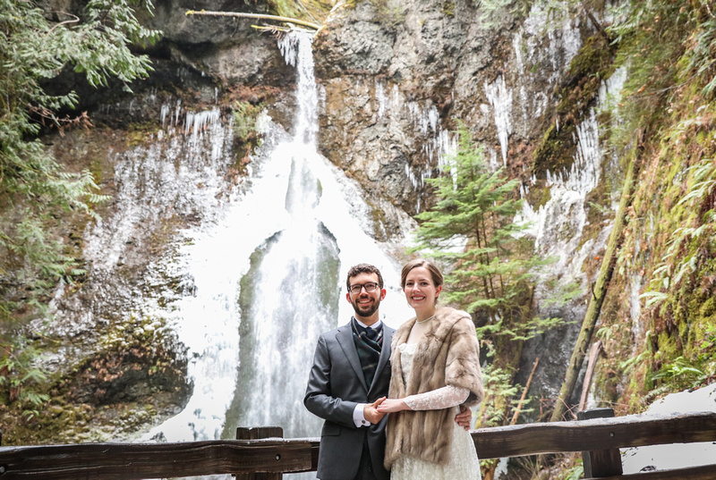 Wedding photography, a bride and groom stand in front of a waterfall.