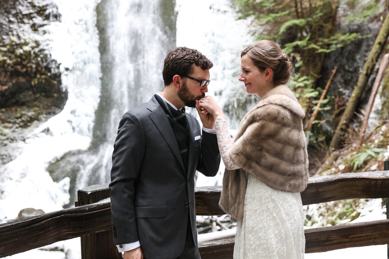 Wedding photography, a groom kisses his wife's hand in front of a winter waterfall in Washington.
