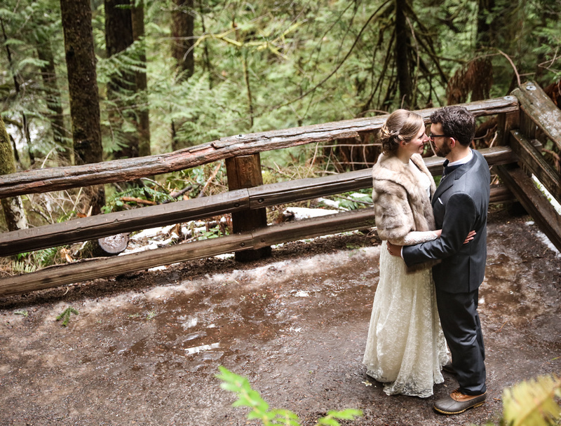 Wedding photography, a bride and groom hold each other romantically in the woods.