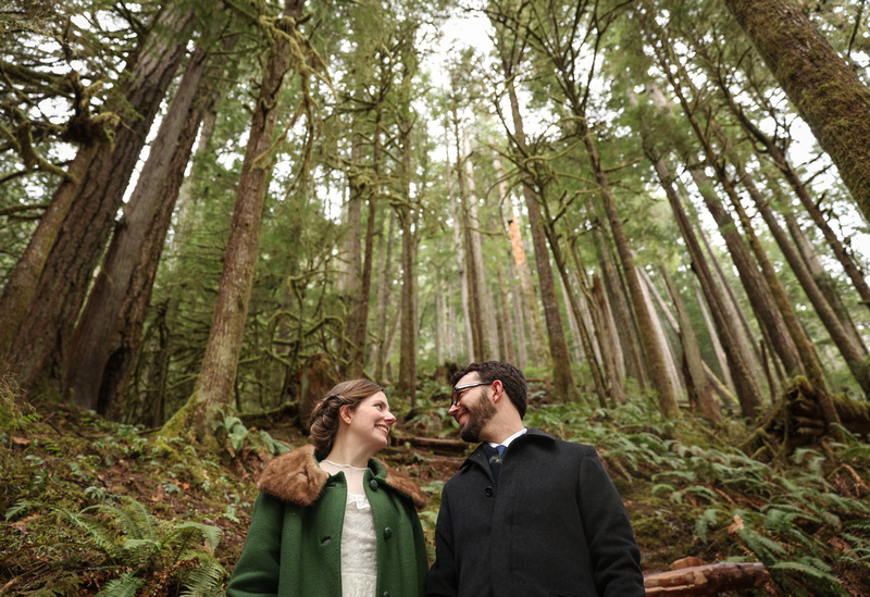 Wedding photography: a bride in a green coat and groom look at each other and smile. They are surrounded by a forest of trees.