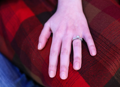 Wedding photography, a woman's hand, with an engagement ring, on her red plaid skirt.