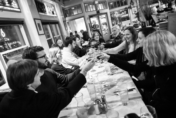 Wedding photography, a group of family and friends toast glasses, smiling.