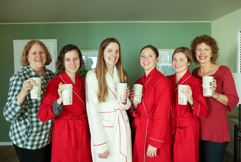 Wedding photography, a smiling wedding party poses in red robes with matching mugs.