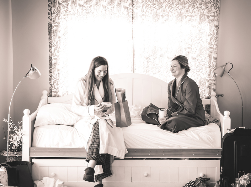 Wedding photography, a long-haired bride opens a gift from her friend, who is laughing.