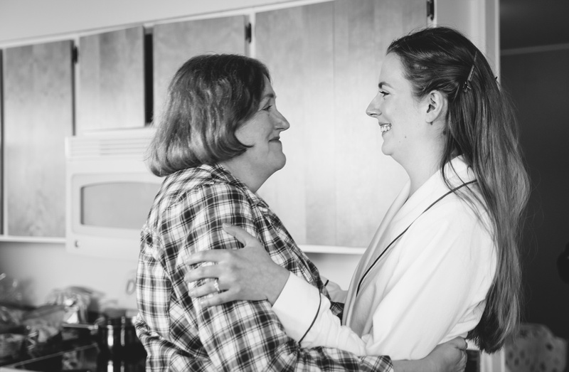 Wedding photography, a bride in her bathrobe smiles with her mother, who is emotional.