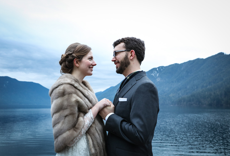 Wedding photography, a bride in a lace gown with a fur stole holds her husband's hands by the water.