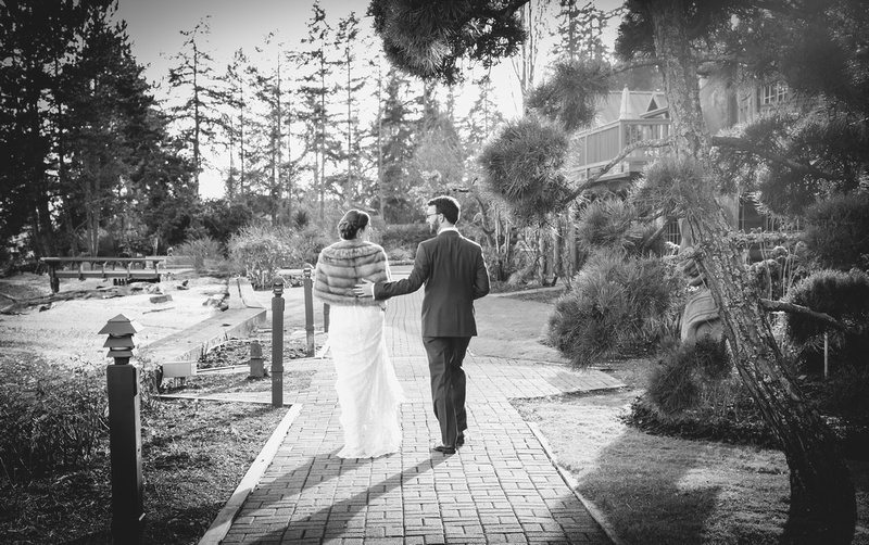 Wedding photography, a bride and groom walk away down a tree-lined path.