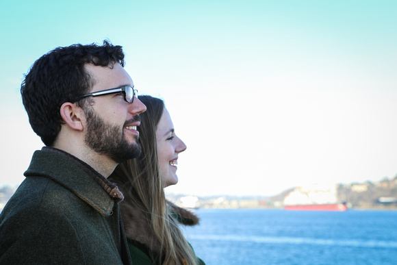 Wedding photography, a couple smiles as they look at the water from a boat.