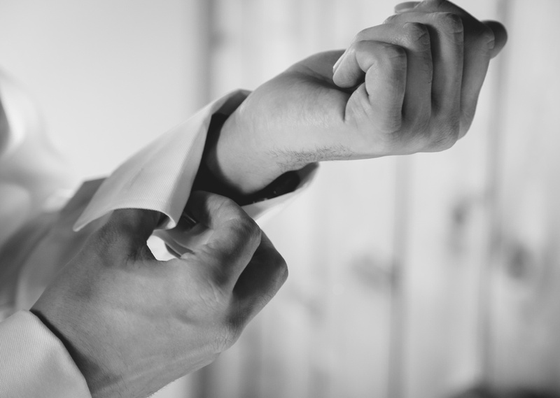 Wedding photography, a close-up of a groom fixing his cuff links.