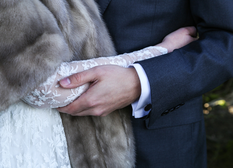 Wedding photography, a closeup of a bride and groom's arms holding each other. She wears a lace gown.