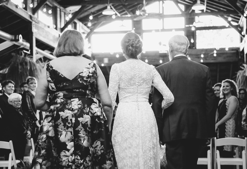 Wedding photography, a bride walking down the aisle with her parents.