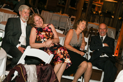 Wedding photography, the parents of the bride and groom sit in chairs watching them dance.