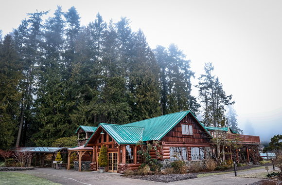 Wedding photography, a lodge in the forest with morning mist hovering over it.