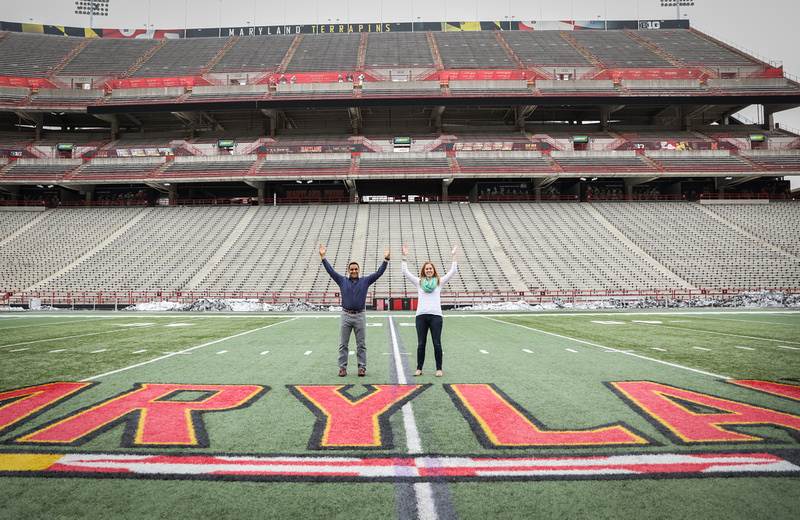Engagement photography, a couple makes the field goal symbol on the football field.