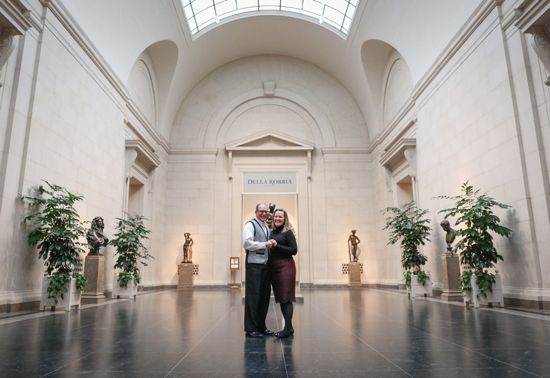Engagement photography, a couple smiles at the camera, standing in an open museum space.