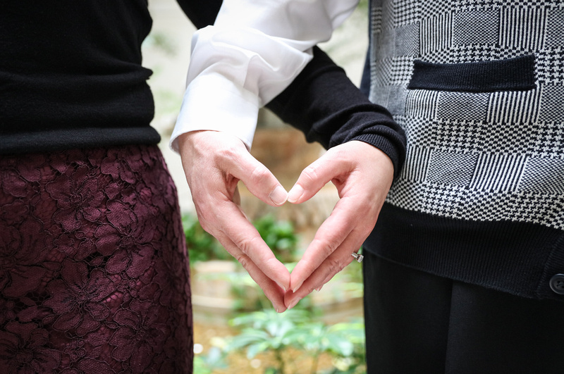Engagement photography, a couple makes the shape of a heart with their hands. She wears a purple lace skirt.