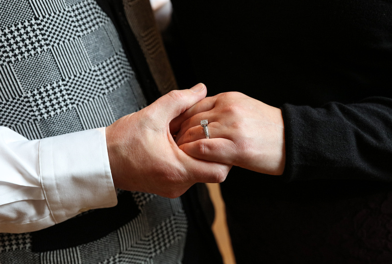 Engagement photography, a closeup on a couple holding hands. She wears a diamond ring.