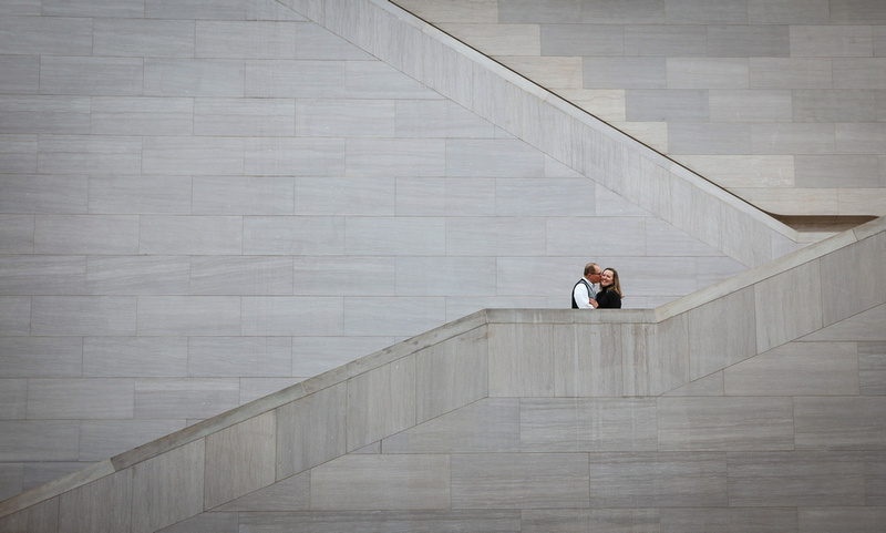 Engagement photography, a couple kisses on an escalator with a large grey wall.