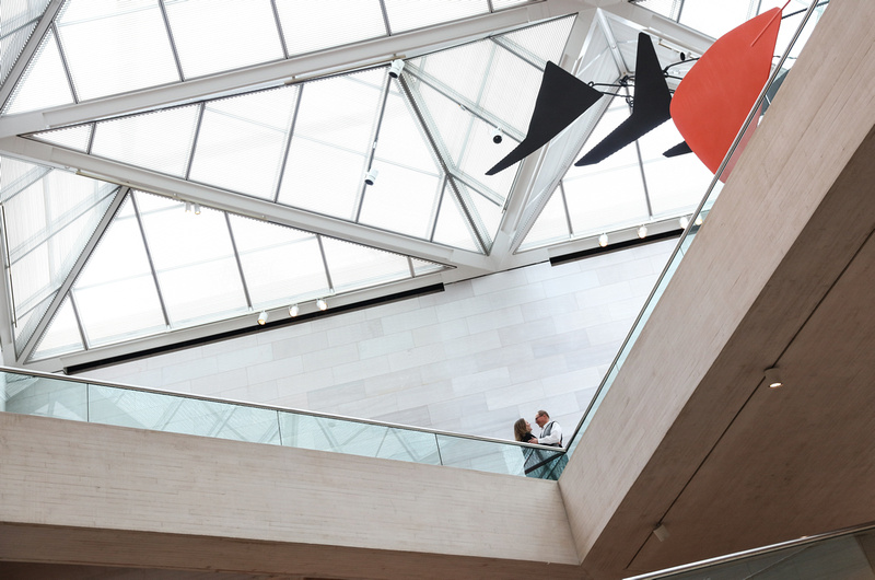 Engagement photography, a couple stands up on a higher level in front of a glass ceiling.